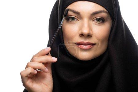 Photo pour Jeune femme musulmane en hijab appliquant le mascara sur les cils isolés sur blanc - image libre de droit
