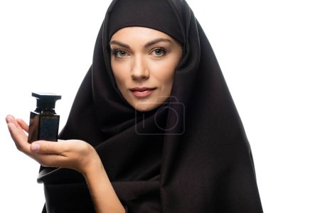 Photo for Young Muslim woman in hijab holding bottle of perfume isolated on white - Royalty Free Image
