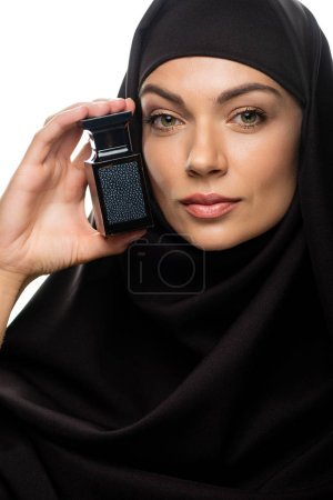 Photo pour Jeune femme musulmane en hijab tenant un flacon de parfum isolé sur blanc - image libre de droit