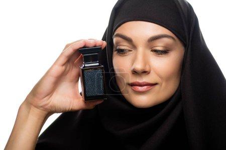 Photo pour Jeune musulmane en hijab regardant une bouteille de parfum isolée sur - image libre de droit
