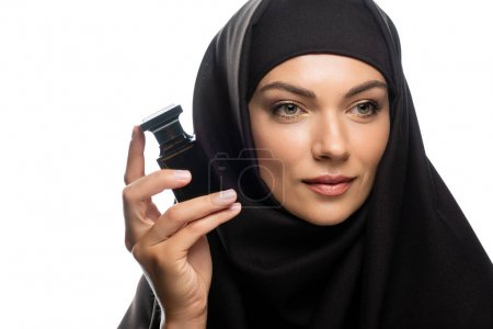 Photo for Young Muslim woman in hijab holding bottle of perfume and looking away isolated on white - Royalty Free Image