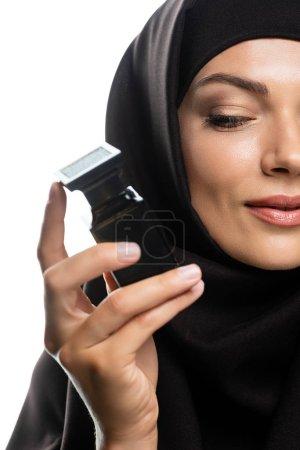 Photo pour Vue partielle d'une jeune musulmane en hijab tenant une bouteille de parfum isolée sur blanc - image libre de droit