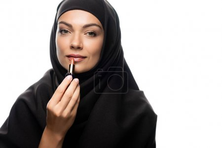 Photo for Young Muslim woman in hijab applying beige lipstick isolated on white - Royalty Free Image