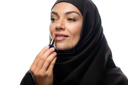 Photo pour Jeune musulmane souriante en hijab appliquant un rouge à lèvres beige isolée sur blanc - image libre de droit