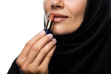 Photo pour Crochet vue d'une jeune musulmane en hijab appliquant un rouge à lèvres beige isolée sur blanc - image libre de droit