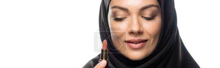 Photo pour Jeune musulmane en hijab tenant un rouge à lèvres beige isolé sur une pellicule blanche panoramique - image libre de droit