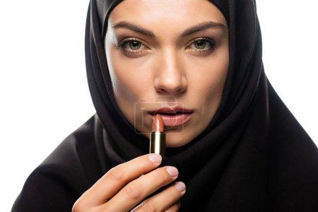 Photo pour Jeune musulmane en hijab appliquant un rouge à lèvres beige isolée sur blanc - image libre de droit