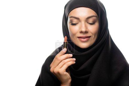 Photo pour Une jeune musulmane souriante en hijab tenant un rouge à lèvres beige isolé sur blanc - image libre de droit