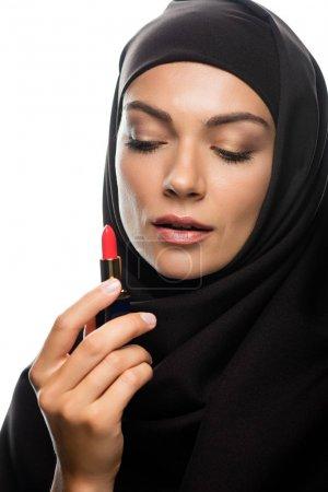 Photo pour Une jeune musulmane en hijab regarde un rouge à lèvres isolé sur un blanc - image libre de droit