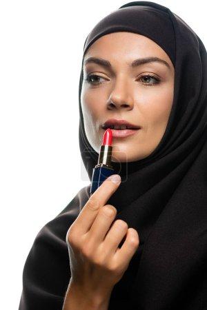 Photo pour Jeune musulmane en hijab appliquant un rouge à lèvres isolée sur blanc - image libre de droit