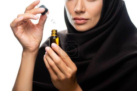 Photo pour Vue recadrée de la jeune musulmane en hijab tenant compte compte compte-gouttes d'une bouteille avec sérum isolé sur blanc - image libre de droit