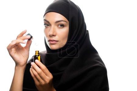 Photo pour Jeune musulmane en hijab tenant une goutte d'eau une bouteille avec du sérum isolé sur blanc - image libre de droit