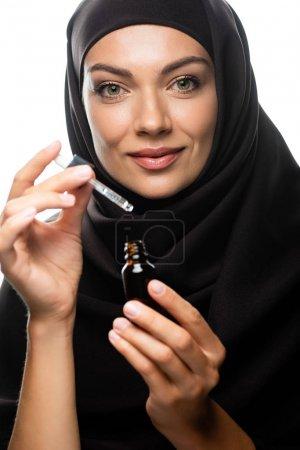 Photo pour Souriant jeune femme musulmane en hijab tenant compte compte compte-gouttes une bouteille avec du sérum isolé sur blanc - image libre de droit