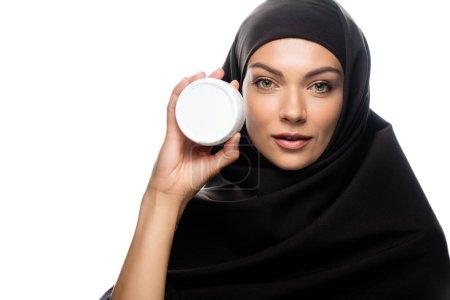 Photo pour Jeune femme musulmane en hijab tenant récipient avec crème cosmétique isolé sur blanc - image libre de droit