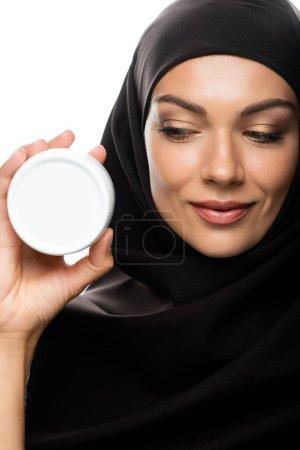Photo pour Une jeune musulmane souriante dans un récipient de hijab contenant de la crème cosmétique isolée sur - image libre de droit