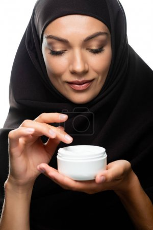 Photo for Young Muslim woman in hijab holding container with cosmetic cream isolated on white - Royalty Free Image