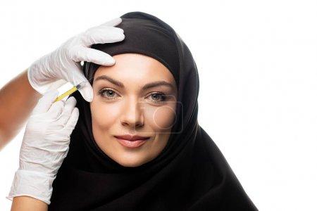Photo pour Jeune musulmane en hijab ayant une injection de beauté isolée sur blanc - image libre de droit