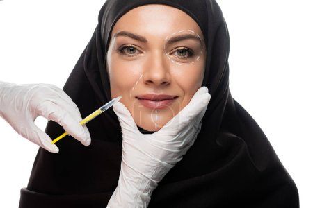 Photo pour Smiling young Muslim woman in hijab with marks on face having beauty injection isolated on white - image libre de droit
