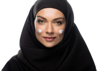 Photo pour Jeune femme musulmane en hijab avec crème cosmétique sur les poussins isolés sur blanc - image libre de droit