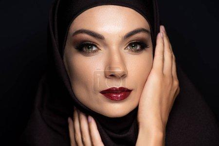 Photo pour Jeune musulmane en hijab avec yeux fumés et lèvres rouges isolées sur noir - image libre de droit