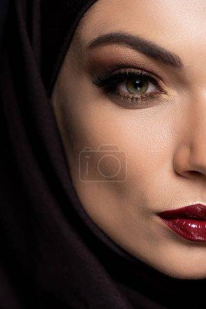 Photo pour Voir de près une jeune musulmane en hijab aux yeux enfumés et aux lèvres rouges isolées sur noir - image libre de droit