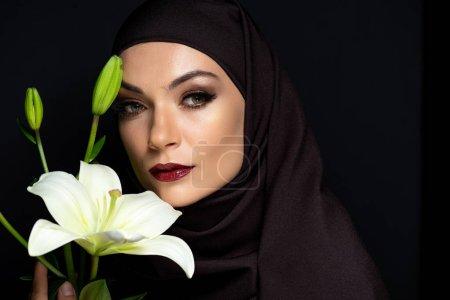 Photo pour Belle musulmane en hijab aux yeux enfumés et aux lèvres rouges tenant le lis isolé sur noir - image libre de droit