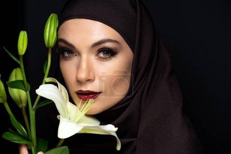 Photo pour Jolie femme musulmane en hijab avec des lèvres rouges tenant lis isolé sur noir - image libre de droit