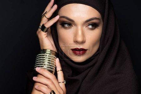 Foto de Hermosa mujer musulmana secuestrada con maquillaje en anillos dorados y pulsera aislada sobre negro. - Imagen libre de derechos