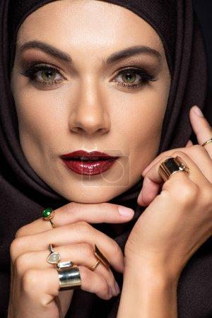 Photo pour Belle femme musulmane en hijab avec maquillage en anneaux d'or isolé sur noir - image libre de droit