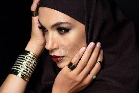 Photo pour Belle musulmane en hijab avec maquillage en anneaux dorés et bracelet isolé sur noir - image libre de droit