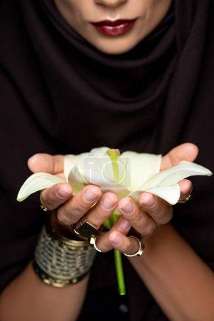 Photo pour Belle femme musulmane en hijab en bagues dorées et bracelet tenant lys isolé sur noir - image libre de droit