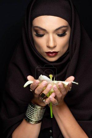 Foto de Hermosa mujer musulmana secuestrada en anillos dorados y pulseras que mantienen levemente aislados sobre negro. - Imagen libre de derechos