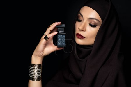 Photo for Beautiful Muslim woman in hijab with makeup in golden jewelry holding perfume isolated on black - Royalty Free Image