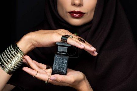 Photo pour Crocheté vue de belle femme musulmane en hijab avec maquillage en bijoux dorés tenant parfum isolé sur noir - image libre de droit