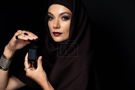 Photo pour Belle femme musulmane en hijab avec maquillage en bijoux dorés tenant parfum isolé sur noir - image libre de droit