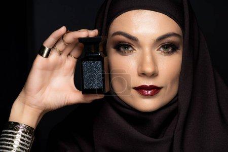 Photo pour Belle musulmane en hijab avec maquillage en bijoux dorés tenant parfum isolé sur noir - image libre de droit