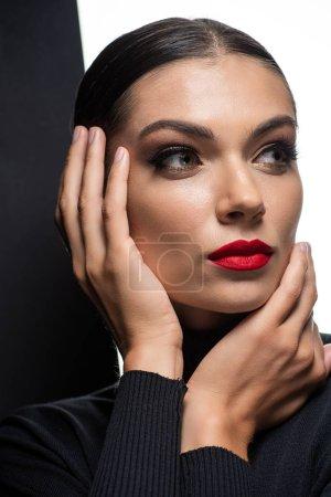 Photo pour Belle femme aux lèvres rouges posant avec les mains près du visage isolé sur blanc et noir - image libre de droit