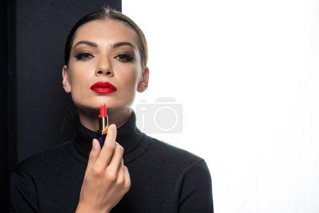 Photo pour Belle femme aux lèvres rouges tenant le rouge à lèvres isolée sur blanc et noir - image libre de droit