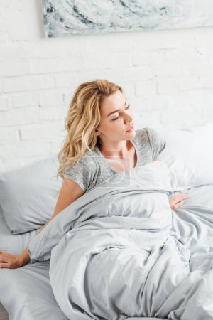 Photo for Attractive young woman waking up in bed at home - Royalty Free Image