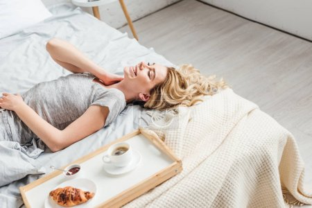 happy girl lying on bed near croissant with cup of coffee on tray