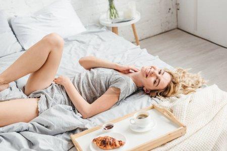 Photo pour Fille positive couchée sur le lit près croissant avec tasse de café sur plateau - image libre de droit