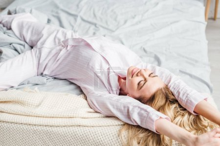 Photo for Cheerful young woman smiling while lying on bed - Royalty Free Image