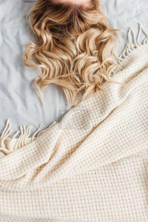 Photo pour Vue recadrée de la femme blonde couchée sur le lit - image libre de droit
