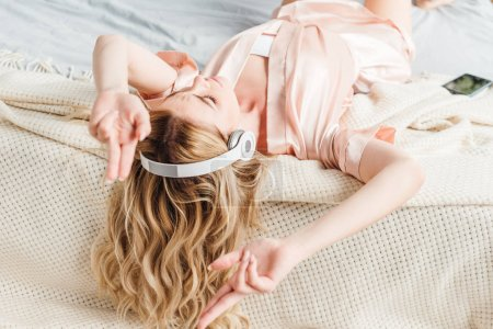 Photo for Selective focus of girl listening music while lying on bed - Royalty Free Image