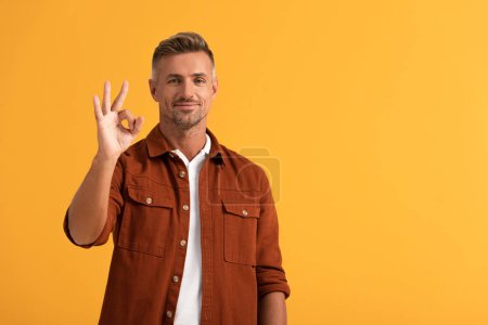 Photo for Cheerful man showing ok sign isolated on orange - Royalty Free Image