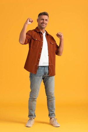 Photo pour Homme gai debout avec les poings serrés sur orange - image libre de droit