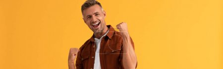 Photo for Panoramic shot of excited man with clenched fists isolated on orange - Royalty Free Image