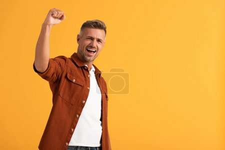 Photo for Excited man with clenched fist celebrating isolated on orange - Royalty Free Image