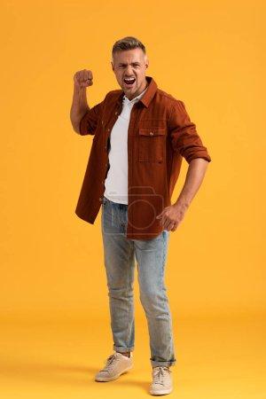 Photo pour Homme en colère avec poing serré criant sur orange - image libre de droit