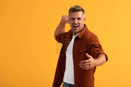 Photo pour Homme en colère avec poing serré hurlant isolé sur orange - image libre de droit